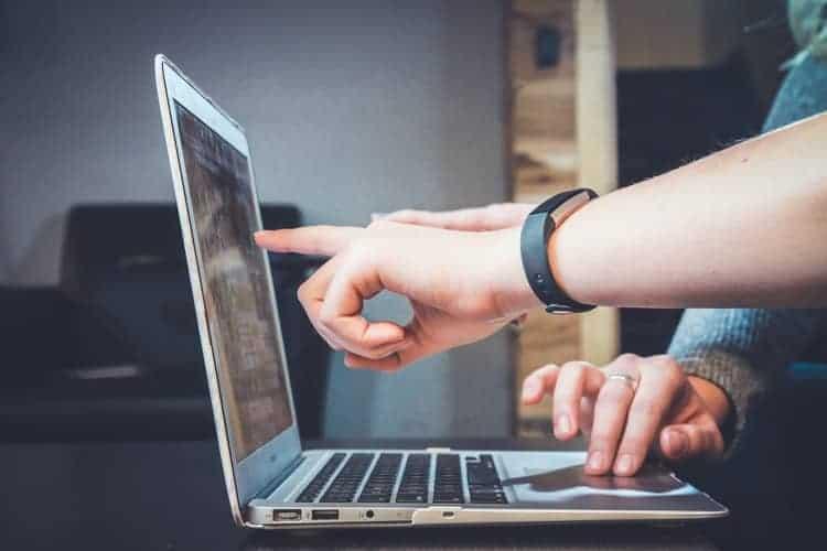 people touching laptop screen